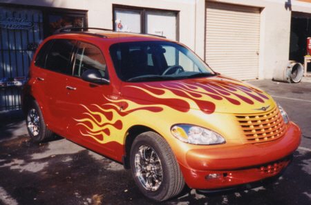 Side of small red car with yellow flame paint job
