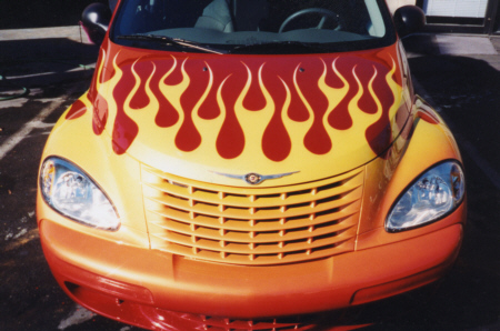 Front of small red car with airbrush painted yellow flame paint job